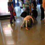 Criança adormece em cima da mala de viagem