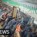 Passageiros levantam carruagem para libertar homem preso junto à plataforma